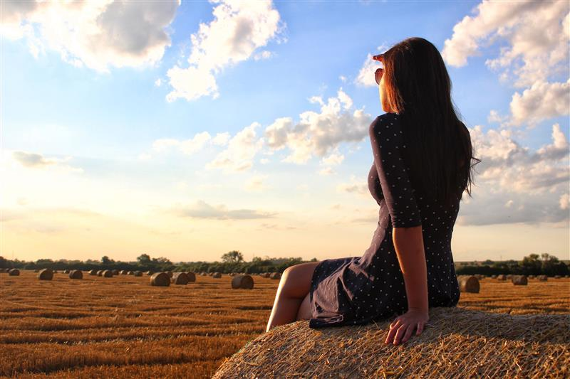 Woman sitting on haystack and watching the sunset #2