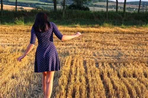 Woman walking on a mown field at sunset