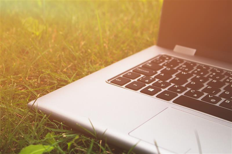 Laptop on grass in sunlight