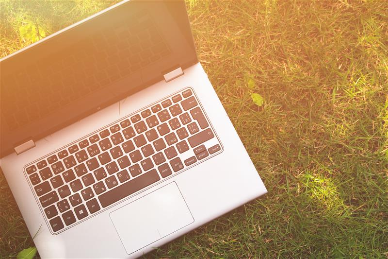 Open laptop on grass in sunlight