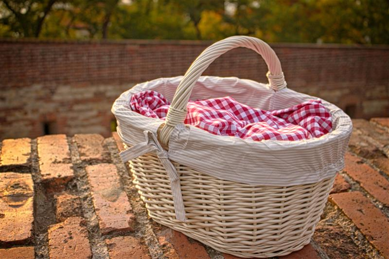 White picnic basket on brick wall at sunset