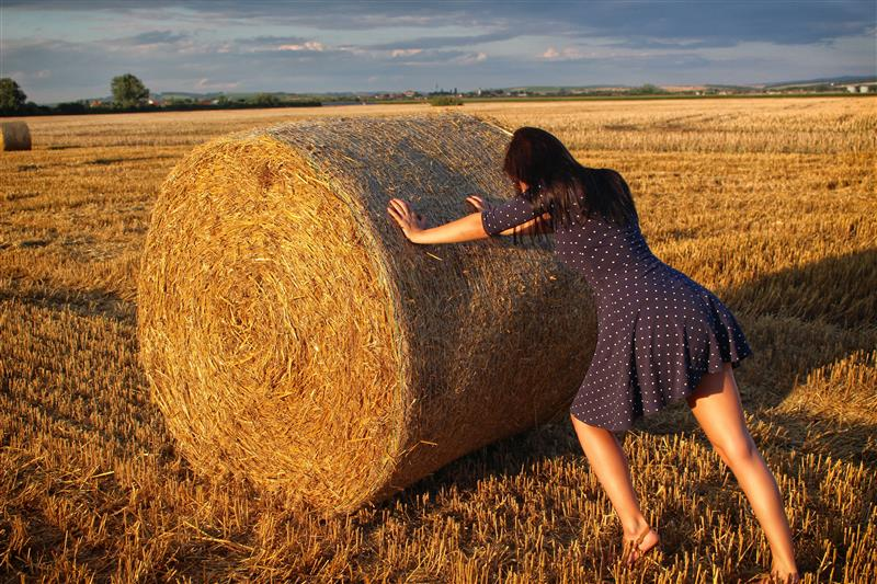 Woman pushing the haystack at sunset