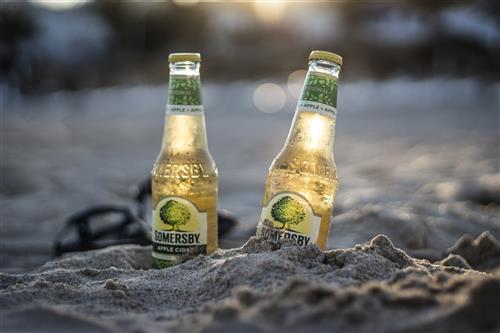 Apple cider bottles on the beach in summer evening with sunset
