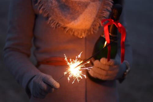 Woman holding champagne and a lit sparkler