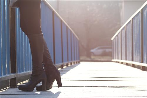 Woman in high heel boots on the bridge